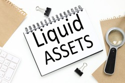Liquid Assets. text on notepad on white background