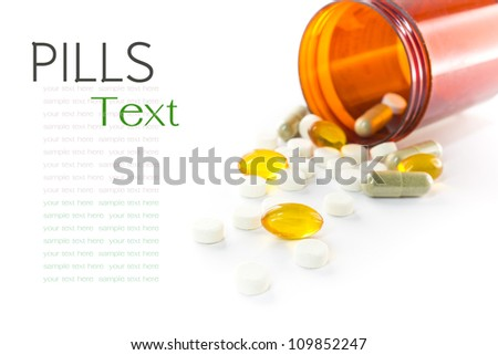 Liquid capsules and pills spilling out of bottle on white background