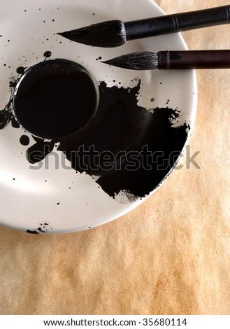 Liquid China ink in the saucer with two calligraphy brushes