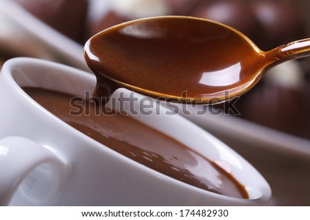 Liquid chocolate dripping from the spoon in a cup closeup horizontal. macro