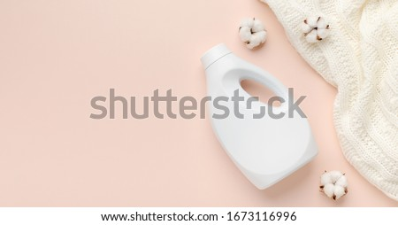 Liquid detergent bottle and white wool sweater. Fabric softener. Regular washing. Laundry concept. Empty place for text or logo on pastel pink background, panorama Foto stock ©