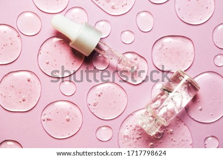 Liquid gel or serum drops with pipette on pink background in macro. Flat lay style.