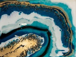 liquid marble background. Streams of blues, whites and golds, meandering metallic curls and foamy splashes of color form the landscape of these flowing textures. waves of turquoise and blue