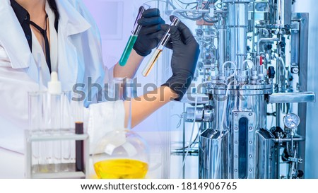 Liquid obtained in the fermentation process. Microbiologist with test tubes in his hands. Chemical laboratory equipment. Laboratory bioreactor for the production of vaccines. Pharmacology.
