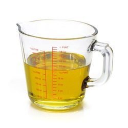Liquid oil in measuring cup isolated on white background