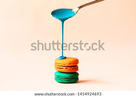 Liquid paint spills from a spoon on a macaroon on a pastel pink background. Copy space for text. Sweets in the modern version with the trend of receiving fluid liquids. #1454924693