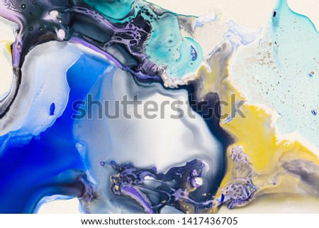Liquid paper yellow purple blue paint background. Fluid painting abstract texture, art technique. Colorful mix of acrylic vibrant colors. Creativity and painting. Background design, printing, pattern