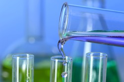 Liquid pouring into test tube from graduated cylinder in laboratory