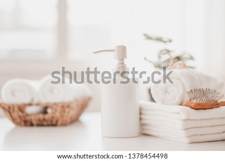 Liquid soap bottle, white towel on basket in bathroom. Hygiene and healthy life concept. Close up, selective focus #1378454498