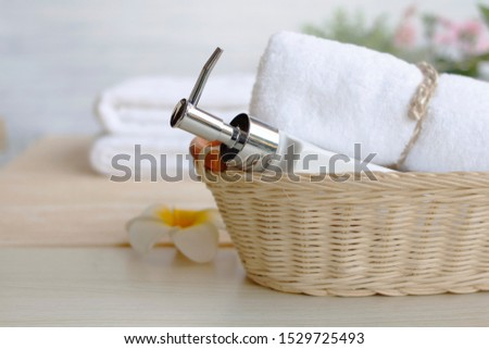 Liquid soap bottles placed in a basket on a wooden table. With roll towels Spa and health concepts
