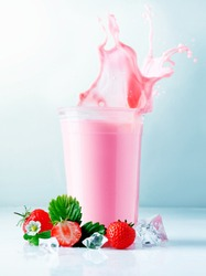 Liquid splashing out of a glass filled with delicious healthy blended strawberry smoothie served with ripe whole fruit
