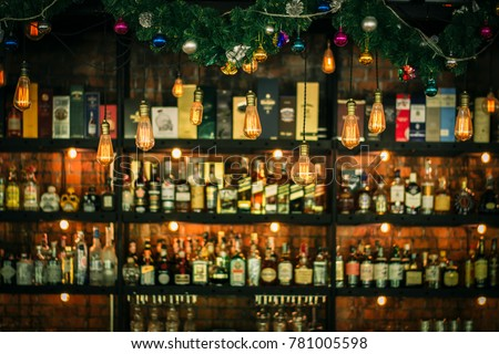 Liquor bar and many alcohol drinks behind the bar with vintage lamps #781005598