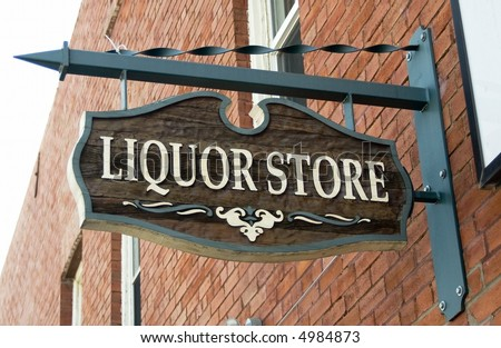 Liquor store sign hanging on a red brick wall.