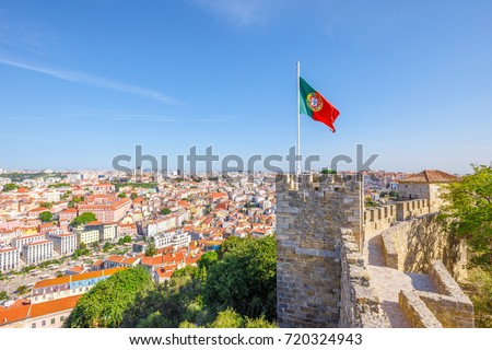 Lisbon aerial view cityscape with Portugal flag waving on ancient fortress wall of Sao Jorge Castle, at Moorish castle on highest hill in Alfama. Lisbon Castle is a popular tourist attraction. #720324943