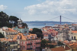 Lisbon. Bridge and Jesus Christ in background. Rooftops. Sunny spring day.