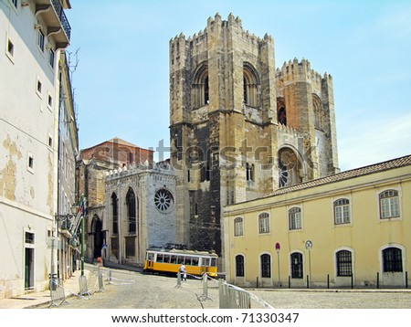 Lisbon Cathedral (Santa Maria Maior) and traditional yellow tram on the street, Portugal
