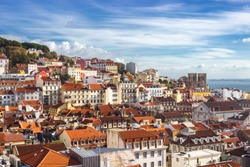 Lisbon cityscape, view of the old town Alfama, Portugal, panorama.Lisboa colorful houses and red-tiled roofs. Hills with trees and historical buildings on a sunny day. Rooftops of the Portuguese city.