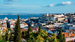 Lisbon, Portugal cityscape overlooking Baixa downtown area. Visible landmarks include: Rua Augusta Triumphal Arch, Rossio, Santa Justa Elevator and Chiado with Tagus River at background