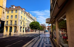 Lisbon Portugal. Empty wide street with storefront shop and yellow building. Scenic cityscape with blue sky.