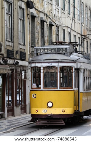LISBON, PORTUGAL - MARCH 27: Old yellow tram on the street of Lisbon, Portugal at March 27, 2011. The yellow trams were imported from the United States in 1901 to replace horse-drawn carriages. - stock photo
