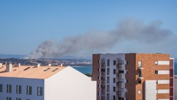 Lisbon, Portugal. Massive dry forest fire near the residential houses. Thick black smoke plumes drifting to the Atlantic Ocean side. Dangerous and deadly wildfires often spread throughout the country.