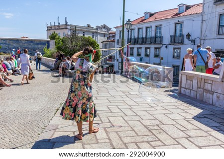 LISBON, PORTUGAL - MAY 27, 2015: A person entertain the crowd gathered at Largo das Portas do Sol in Lisbon Portugal. Outdoor entertainment is the part of European culture.