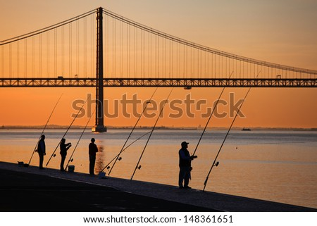 LISBON, PORTUGAL - MAY 05: angler at river Tagus with view on the 25th of April Bridge on May 05, 2013 in Lisbon. The bridge is 2.277 meters long and the 23. largest suspension bridge in the world