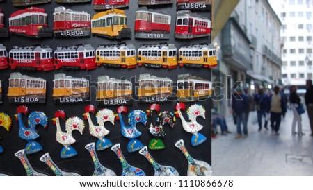 Lisbon street. Magnetic trams and Galo de Barcelos (Barcelos Rooster). Typical souvenir of Lisbon.           #1110866678