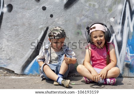 listen to music abstract concept with singing children against graffiti wall