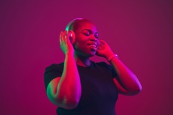 Listen to music. African-american young woman's portrait on purple background. Beautiful model in wireless headphones. Concept of emotions, facial expression, sales, ad, inclusion. Copyspace.