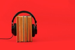 listen to the audio books concept, big headphones put on the stack of books isolated, simple style