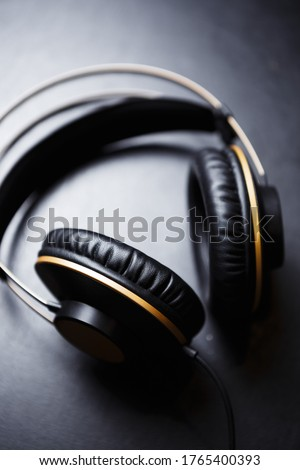 Listen to the music with professional headphones.Big black headset with golden frame for audiophile.Enjoy musical tracks in high fidelity with analog hifi head monitors in sound recording studio