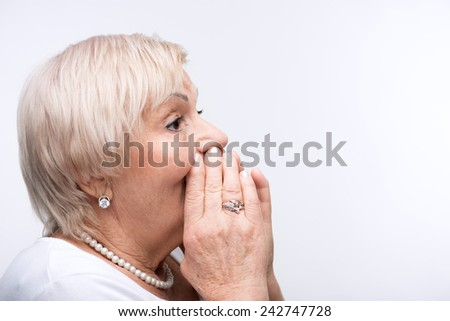 Listen up. Closeup portrait of elderly woman cupping her hands on mouth directing to copy space while standing against white background