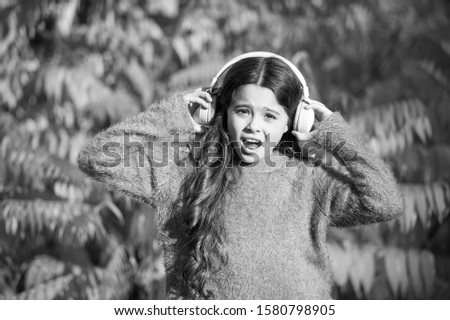 Listening audio best way help child improve vocabulary. Kid girl relaxing near autumn tree with headphones. Autumn walks with nice songs. Music for autumn mood. Listening song. Enjoy music fall day.