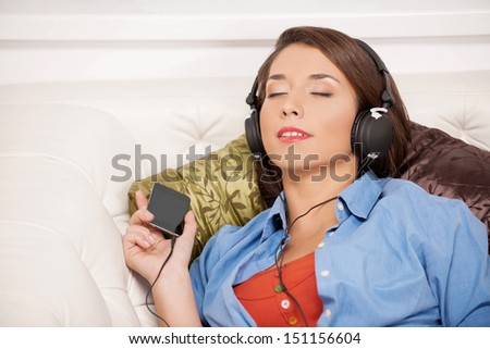 Listening to her favourite music. Beautiful young woman listening to the music and keeping her eyes closed