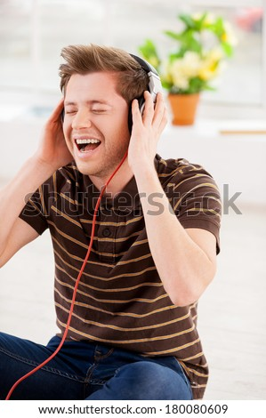 Listening to his favorite music. Happy young man in headphones listening to the music and keeping eyes closed while sitting on the floor at his apartment