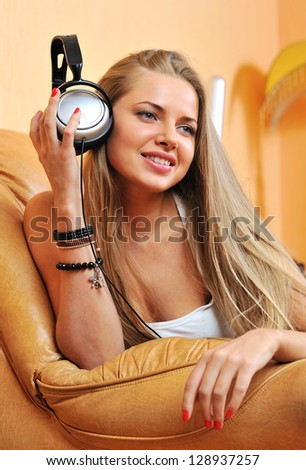 Listening to music - beautiful woman portrait relaxing at home holding headphones and smiling