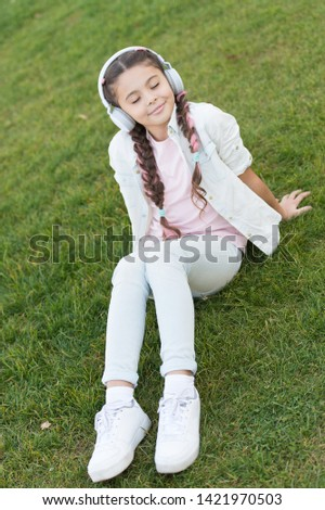 Listening to soft music sound is quite relaxing to me. Small girl listening to sound track on green grass. Little child wearing earphones playing electronic sound. Cute kid enjoying melodious sound.