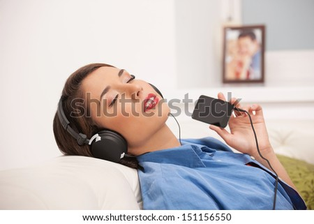 Listening to the music. Beautiful young woman in headphones listening to the music and keeping her eyes closed