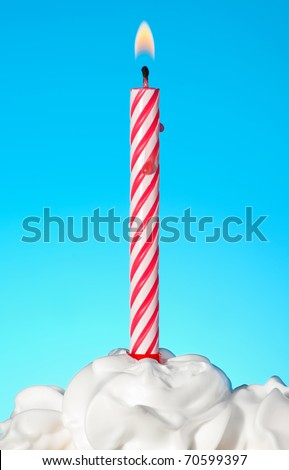Lit birthday candle on blue background