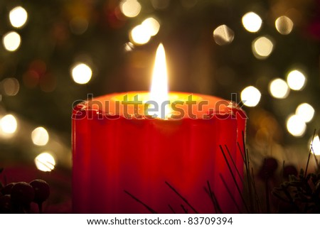 Lit candle on Christmas Eve in front of the diffused lights on a Christmas tree