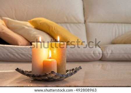 lit candles on a marble table and in the background a sofa with pillows, which