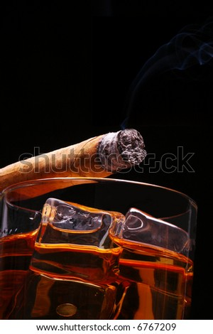 Lit Cigar resting on Glass of Whiskey and Ice cubes with wisp of smoke and black background, low angle - stock photo