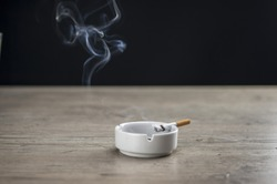 Lit cigarette burning in ashtray close up