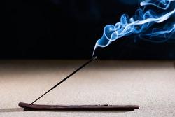 Lit incense stick with smoke on a black background