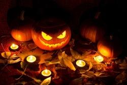 Lit jack-o'-lantern and burning candles. Halloween concept