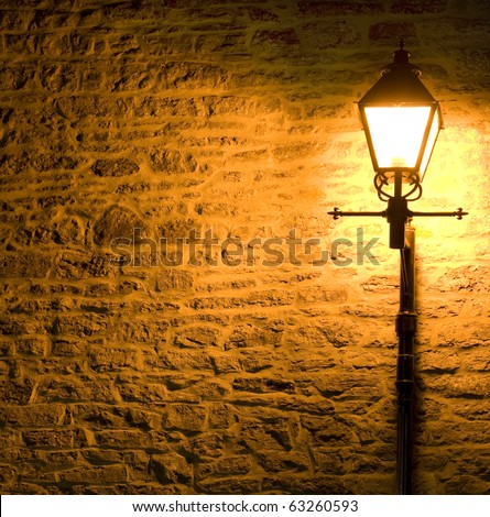 Lit Lamp post against a textured brick wall at night
