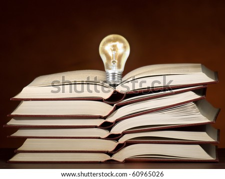Lit light bulb on the stack of books, can be used as concept for education,ideas,solution