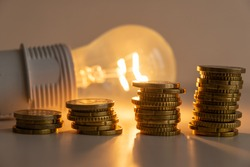 Lit light bulb with coins beside it. Increase in energy tariffs. Efficiency and energy saving.