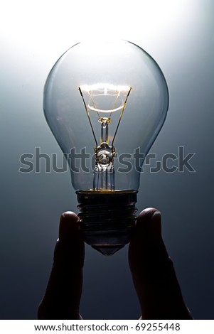 Lit lightbulb held between fingers